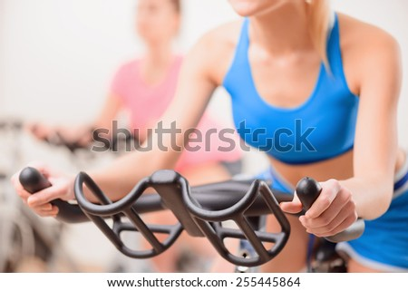 Cycling on exercise bikes. Cropped image of two attractive young women in sports clothing exercising on gym bicycles with selective focus - stock photo