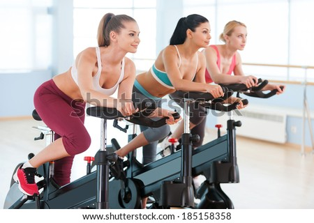 Cycling on exercise bikes. Two attractive young women in sports clothing exercising on gym bicycles - stock photo