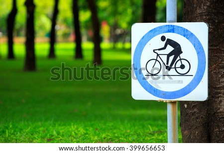 Cycling sign with green grass background.