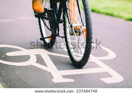 Cycling to work. City bike sign on asphalt bikepath man cycling on road, colorful vintage light on street, commuting to work on bicycle in urban environment - stock photo
