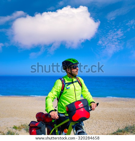 cycling tourist MTB cyclist in Mediterranean beach with paniers and saddlebag