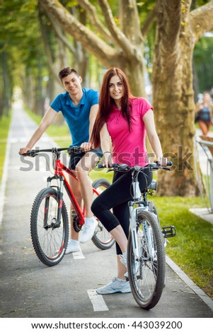 Cycling young couple. In the park.Beautiful bicycle lane
