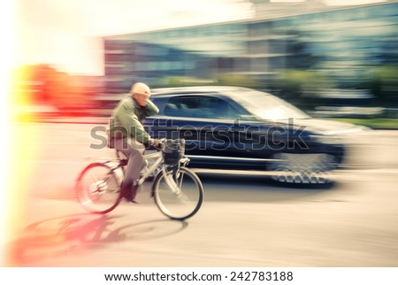 Cyclist and a car on the street. People hurrying about their business. Image in motion blur style. Cross Process stylization.  - stock photo