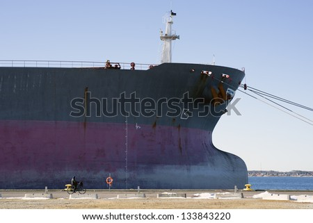Cyclist and big ship - stock photo