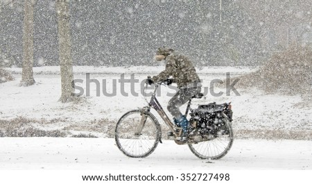 Cyclist biking through the snow in winter