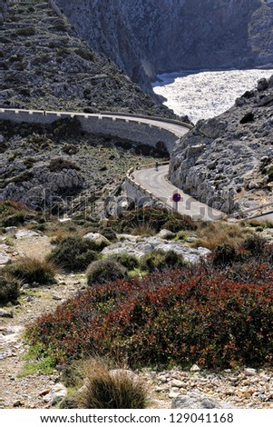 Cyclist climbing the narrow, winding mountain road on the way to Cap Formentor on Mallorca, Balearic Islands, Spain, Europe - stock photo