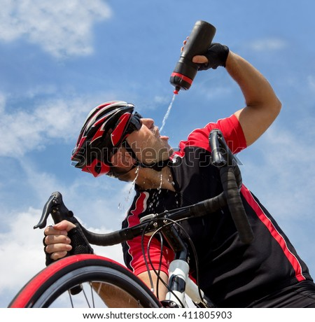 Cyclist drinking from a bottle while riding a bike on blue background.Thirsty bicyclist drinks drink from the bottle.Refreshing the tired cyclists.Biker on bike drinks water from bottle over his head.