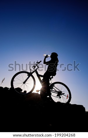 Cyclist drinking water. Silhouette of a man on mountain bike at sunset - stock photo