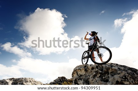 Cyclist drinks water on top of a mountain with bike on a sunny day - stock photo