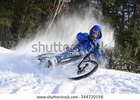 Cyclist extreme riding mountain bike in flying snow near winter forest in sunny cold day  - stock photo