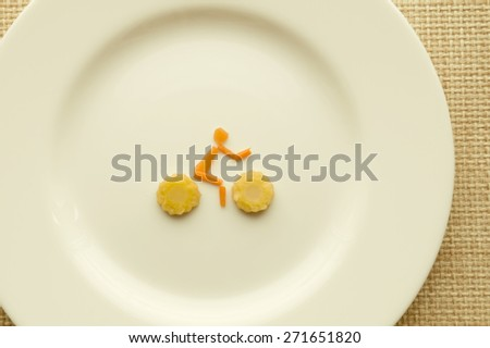 Cyclist from carrots and corn on the white plate - stock photo