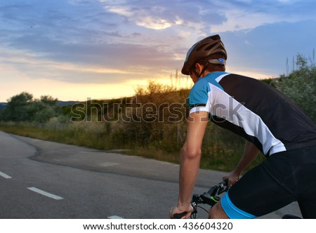 cyclist going mountain bike along a lonely road at sunset