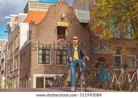 Cyclist in Amsterdam crossing the bridge over canal