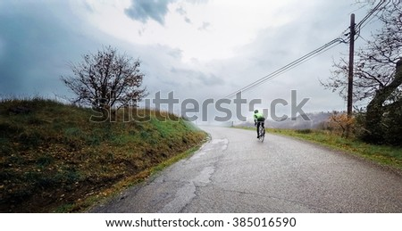 Cyclist in an uphill road during a storm. POV Original point of view - stock photo