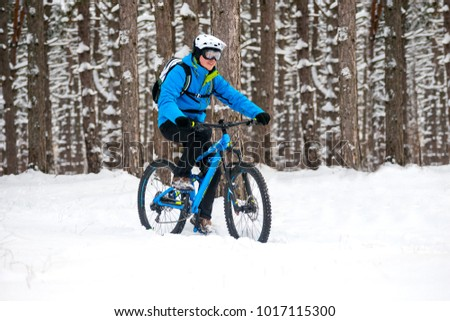 Cyclist in Blue Riding the Mountain Bike in the Beautiful Winter Forest Covered with Snow. Extreme Sport and Enduro Biking Concept.