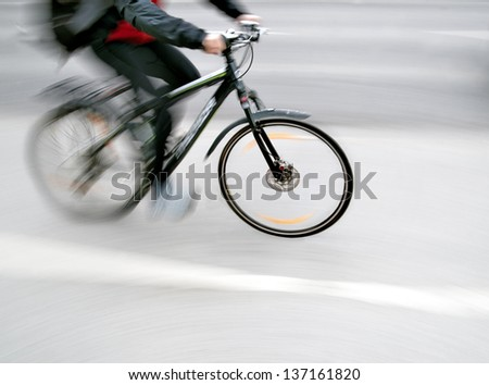 cyclist in blurred motion with neutral background - stock photo