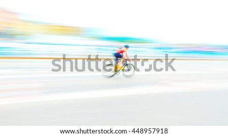 Cyclist in extreme motion blur capture in bright and vivid colors on a city road. Wide angle shot. - stock photo