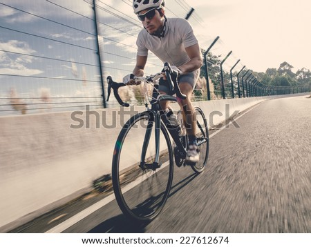 Cyclist in maximum effort in a road outdoors - stock photo