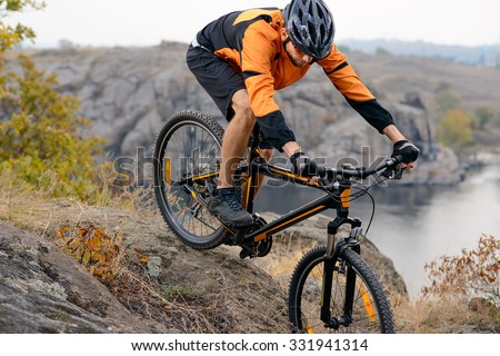 Cyclist in Orange Wear Riding the Bike Down Rocky Hill under River. Extreme Sports Concept. - stock photo