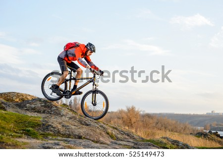 Cyclist in Red Jacket Riding the Bike Down Rocky Hill. Extreme Sport Concept. Space for Text.