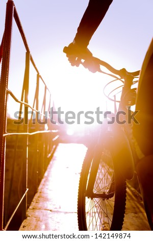 Cyclist in the rays of the setting sun. - stock photo