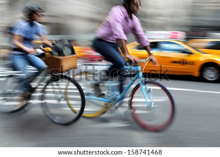 cyclist in traffic on the city roadway < motion blur > - stock photo