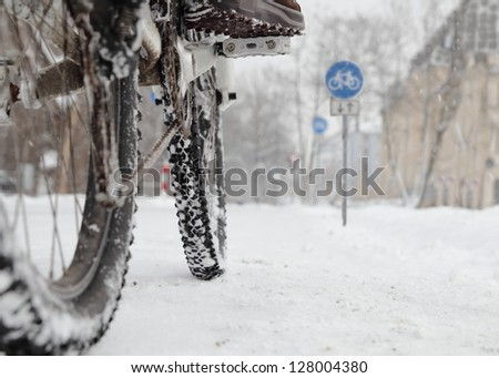 Cyclist in winter with bike road sign low angle - stock photo