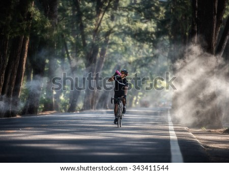 Cyclist is drinking water from the sport bottle - stock photo