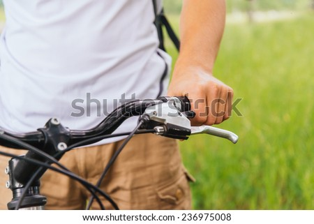 Cyclist male hand holding handlebar of mountain bike in summer park, close-up image, face is not visible - stock photo