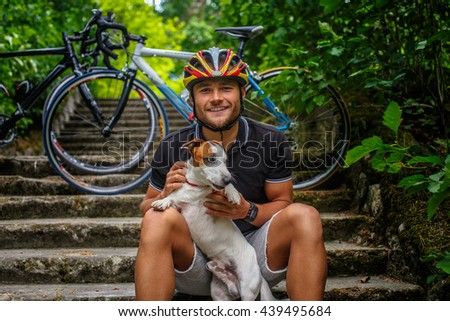 Cyclist male posing with his russel dog on stairs in a forest.