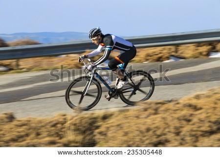 Cyclist man riding mountain bike on a mountain road - stock photo