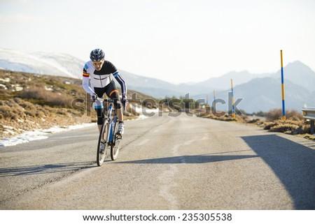 Cyclist man riding mountain bike on a mountain road. - stock photo