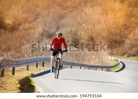 Cyclist man riding mountain bike on asphalt road - stock photo