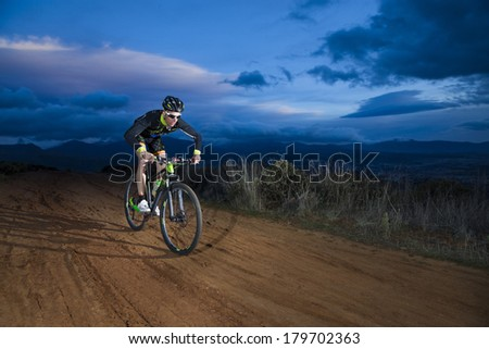 Cyclist man riding mountain bike on mountain.