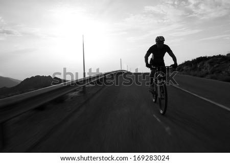 Cyclist man riding mountain on a mountain road, silhouette sunrise. - stock photo