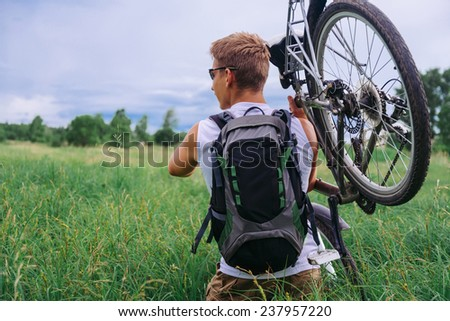 Cyclist man with backpack carries bicycle in green meadow in summer. Theme of sport and hiking