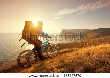 cyclist on a mountain bike travels around the beautiful landscape - stock photo
