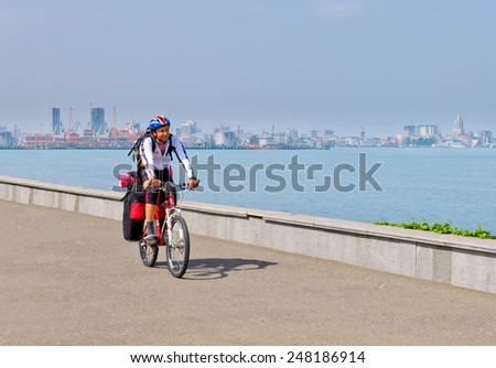 Cyclist on a mountain bike with a large backpack on a background of the sea - stock photo