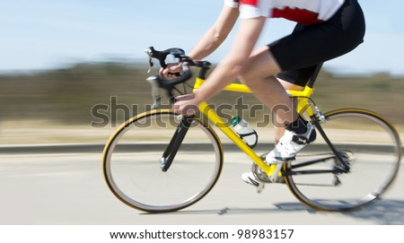 Cyclist on a racing bike speeding past on the verge of a road