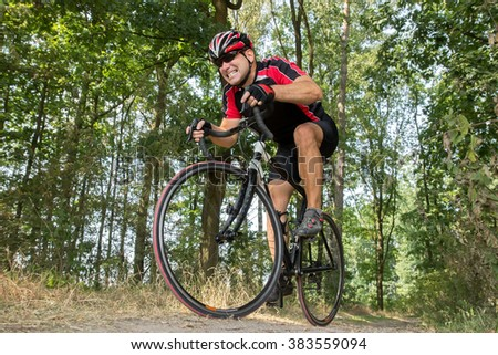 cyclist on a road bike rides in the terrain - stock photo