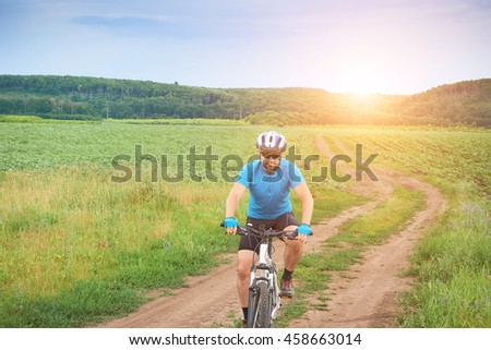 Cyclist on a white bicycle in a blue uniform rides  outdoors.   - stock photo