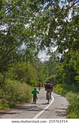 Cyclist on Bike Path - Cyclists circulating bike lane on the outskirts of a city and among trees with sun  - stock photo