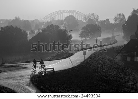 cyclist on dike in foggy morning - stock photo