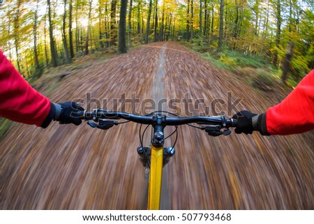 Cyclist on mountain bike riding with speed through autumn forest. Original point of view and motion blur.