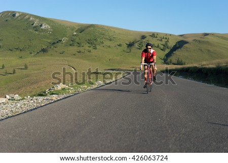 cyclist on road bike climbing the hill on a sunny day - stock photo
