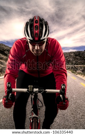 Cyclist on road bike through a asphalt road in the mountains and blue sky with clouds. - stock photo