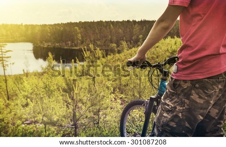 cyclist on the background of forest lake. Focus on the bike. panorama. toned image - stock photo