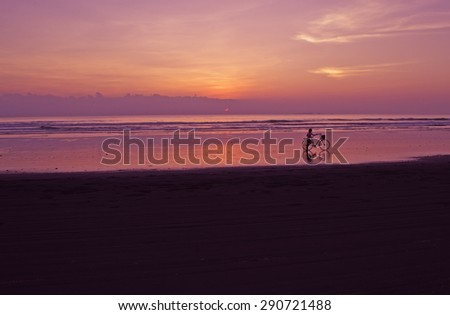 Cyclist on the beach in the sunset