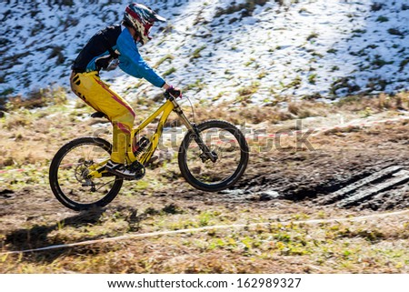Cyclist on the downhill on snow and mud