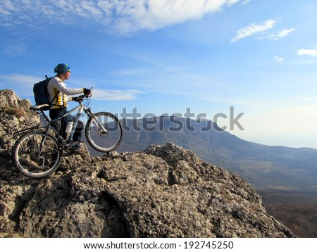 Cyclist on the top of a hill - stock photo